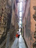 On a rainy summer day, the guide conducts a tour of the narrow street of the coastal city of Manarola. Manarola, Italy, July 30, 2014. On a rainy summer day, the royalty free stock images
