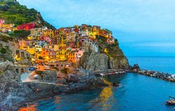 Manarola traditional typical Italian village in National park Cinque Terre. With colorful multicolored buildings houses on rock cliff and marine harbor, night royalty free stock photos