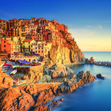 Manarola village, rocks and sea at sunset. Cinque Terre, Italy Stock Photos