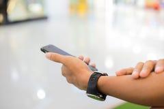 Manasiat som använder telefonen för celling och smsar på hennes mobila phon arkivbild