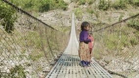 Manaslu, Непал - март 2018: Непальская игра детей на приостанавливанном мосте акции видеоматериалы