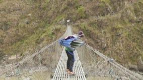 Manaslu, Непал - март 2018: Портер с тяжелыми рюкзаками идет через приостанавливанный мост видеоматериал