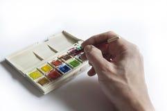 Manassistent genom att använda den bärbara vattenfärguppsättningen Arkivbilder