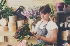 Manassistenten i blomsterhandelleverans gör buketten Royaltyfri Bild