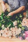 Manassistenten i blomsterhandelleverans gör den rosa bukettcloseupen Fotografering för Bildbyråer