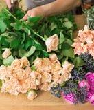 Manassistenten i blomsterhandelleverans gör den rosa bukettcloseupen Royaltyfria Bilder