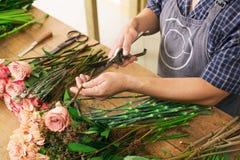 Manassistenten i blomsterhandelleverans gör den rosa bukettcloseupen Arkivbilder