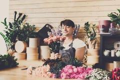 Manassistenten i blomsterhandelleverans gör den rosa buketten Arkivfoto