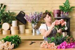 Manassistenten i blomsterhandelleverans gör den rosa buketten Royaltyfri Bild