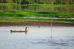 MANAUS, BR, CIRCA AUGUSTUS 2011 - Jongen op een kano op Amazonië riv Stock Afbeelding