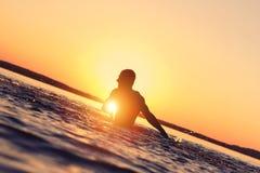 Manbad i vattnet på solnedgången Arkivbild