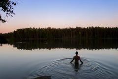 Manbadning i sjövatten på solnedgången royaltyfri bild