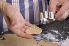 Manbakningkakor hemma i köket arkivfoton