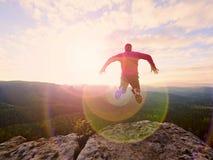 Manbanhoppning från bergkanten Man som hoppar av en klippa utan rep Riskabelt ögonblick Arkivbilder