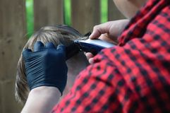 Manbarberaren klipper hans hår med en skrivmaskinspojke arkivbilder