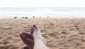 Manbenet har att koppla av på sandstranden i hans ferie fotografering för bildbyråer