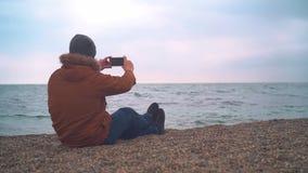 Manblogger i omslaget som sitter på bänk på den sandiga stranden lager videofilmer