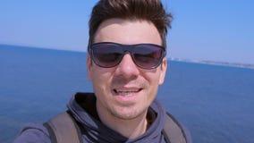 Manbloggerhandelsresande i samtal för solglasögonselfiekamera om semester på havet lager videofilmer