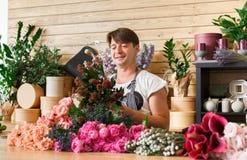 Manblomsterhandlareassistenten i blomsterhandelleverans gör den rosa buketten Fotografering för Bildbyråer