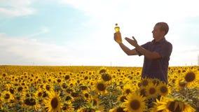 Manbonde som undersöker fältet med solrosor ultrarapidvideo flaska för håll för livsstil för hand för livsstilmanbonde av lager videofilmer