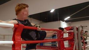 Manboxare som sträcker benet, innan att boxas utbildning på askcirkeln i kampklubba Kickboxer utbildning som sträcker övningen fö lager videofilmer