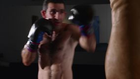 Manboxaredanande slår på en boxningpåse Kämpe som inomhus utbildar arkivfilmer