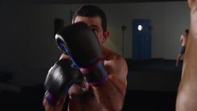 Manboxaredanande slår på en boxningpåse Kämpe som inomhus utbildar stock video