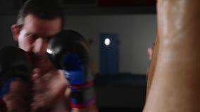 Manboxaredanande slår på en boxningpåse Kämpe som inomhus utbildar lager videofilmer