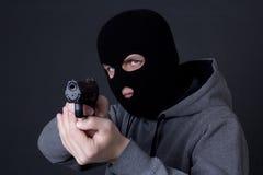 Manbrottsling i den svarta maskeringen som siktar med vapnet över grå färger royaltyfri bild