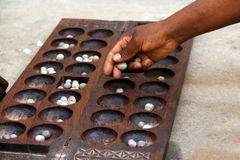 Mancala game. Hand playing Mancala game - a game which is wide spread in Africa and Arabs Royalty Free Stock Images