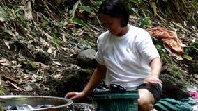 Mancanza di utilità di sistema a acqua pubbliche nelle comunità rurali filippine, forze questa donna per lavare i vestiti anche i stock footage