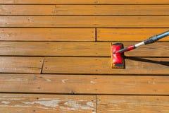 Mancha de madeira com uma almofada da pintura no assoalho de madeira do pátio Imagens de Stock Royalty Free