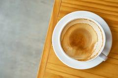 Mancha del café en una taza de café en la tabla de madera Foto de archivo