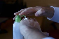 Manchando o creme hidratante nas mãos danificadas de um frasco de creme com o distribuidor fotos de stock