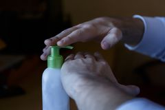 Manchar la crema hidratante en las manos dañadas de un tarro poner crema con el dispensador fotografía de archivo