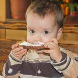 Mancharon al niño mientras que comía El niño está comiendo Poco Imagen de archivo libre de regalías