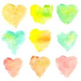 Manchas en forma de corazón de la acuarela aisladas en el fondo blanco Sistema de puntos pintados a mano rojos, amarillos, azules Imagen de archivo