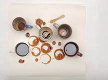 Manchas y palillos mojados del café con las tazas de café en el Libro Blanco Foto de archivo