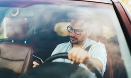 Manchaufför som använder den smarta telefonen i den moderna bilen arkivbild