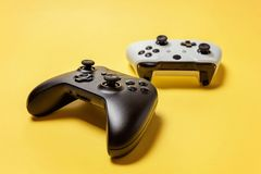 Manche dois branco e preto no fundo amarelo Conceito da confronta??o do controle do videogame da competi??o do jogo do computador foto de stock