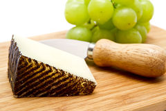 Manchego cheese ang grapes on chopping board Royalty Free Stock Image