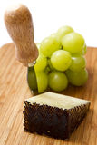 Manchego cheese ang grapes on chopping board Stock Images
