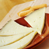 Manchego cheese from Spain. Closeup of an earthenware plate with some slices of manchego cheese from a Spain Royalty Free Stock Images