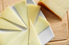 Manchego cheese from Spain. Closeup of a piece and some slices of manchego cheese from Spain stock photo