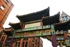 MANCHESTER, ENGLAND - AUGUST 11, 2013: China Town gate with green and golden decoration and painted panels at Manchester city. Center, one of the lagest in the royalty free stock photography