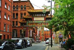 MANCHESTER, ENGLAND - AUGUST 11, 2013: A view to a street with China Town gate with green and golden decoration and painted panels. At Manchester city center royalty free stock photos