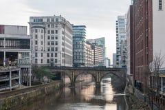 MANCHESTER ENGLAND - MARS 08, 2014: Manchester Cityscape med floden och byggnader Arkivfoto