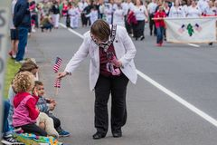 Manchester memorial day parade small town. Parade official hands small boy a united states of america USA flag during memorial day parade royalty free stock photography