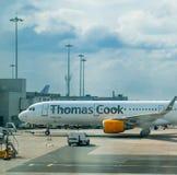 MANCHESTER, REINO UNIDO - 9 DE ABRIL DE 2019: Um avião de Thomas Cook senta passageiros de espera no aeroporto de Manchester fotografia de stock royalty free