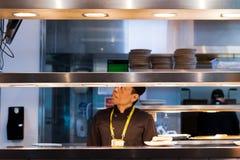 MANCHESTER, REINO UNIDO - 9 DE ABRIL DE 2019: Um cozinheiro chefe em uma cozinha do aeroporto olha uma tela para a ordem seguinte foto de stock royalty free